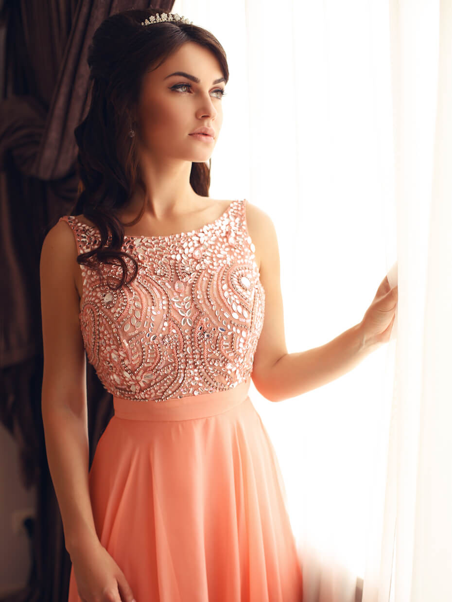 Shutterstock: Woman wearing coral pink prom dress looking out window