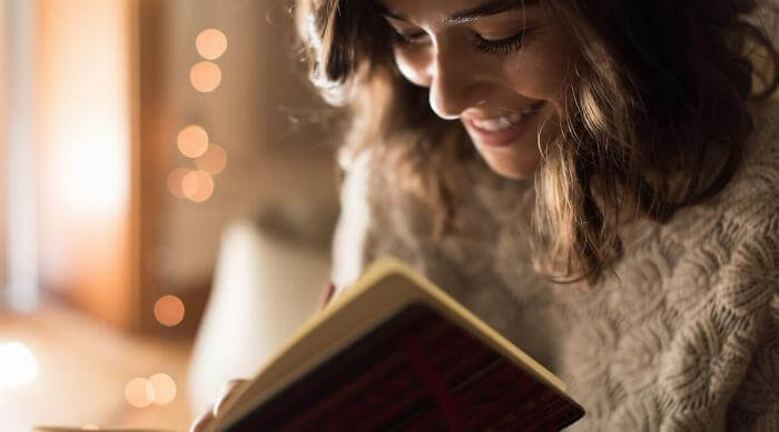 Shutterstock: Woman writing journaling happily in book