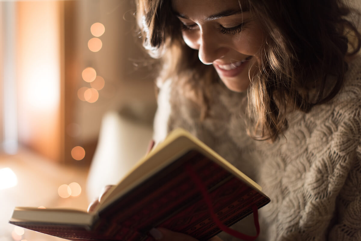 shutterstock-woman-writing-happily-in-book
