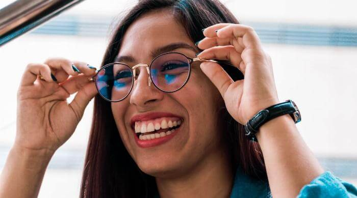 Unsplash: Woman smiling and putting on glasses