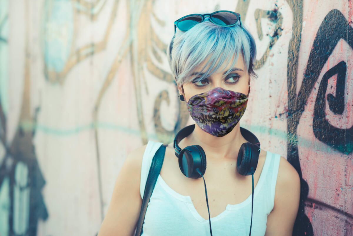 young beautiful short blue hair hipster woman with headphones music in the city wearing myair face mask
