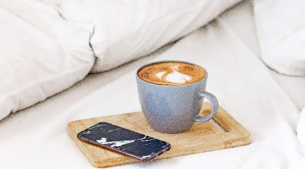 Coffee and phone sitting on bed