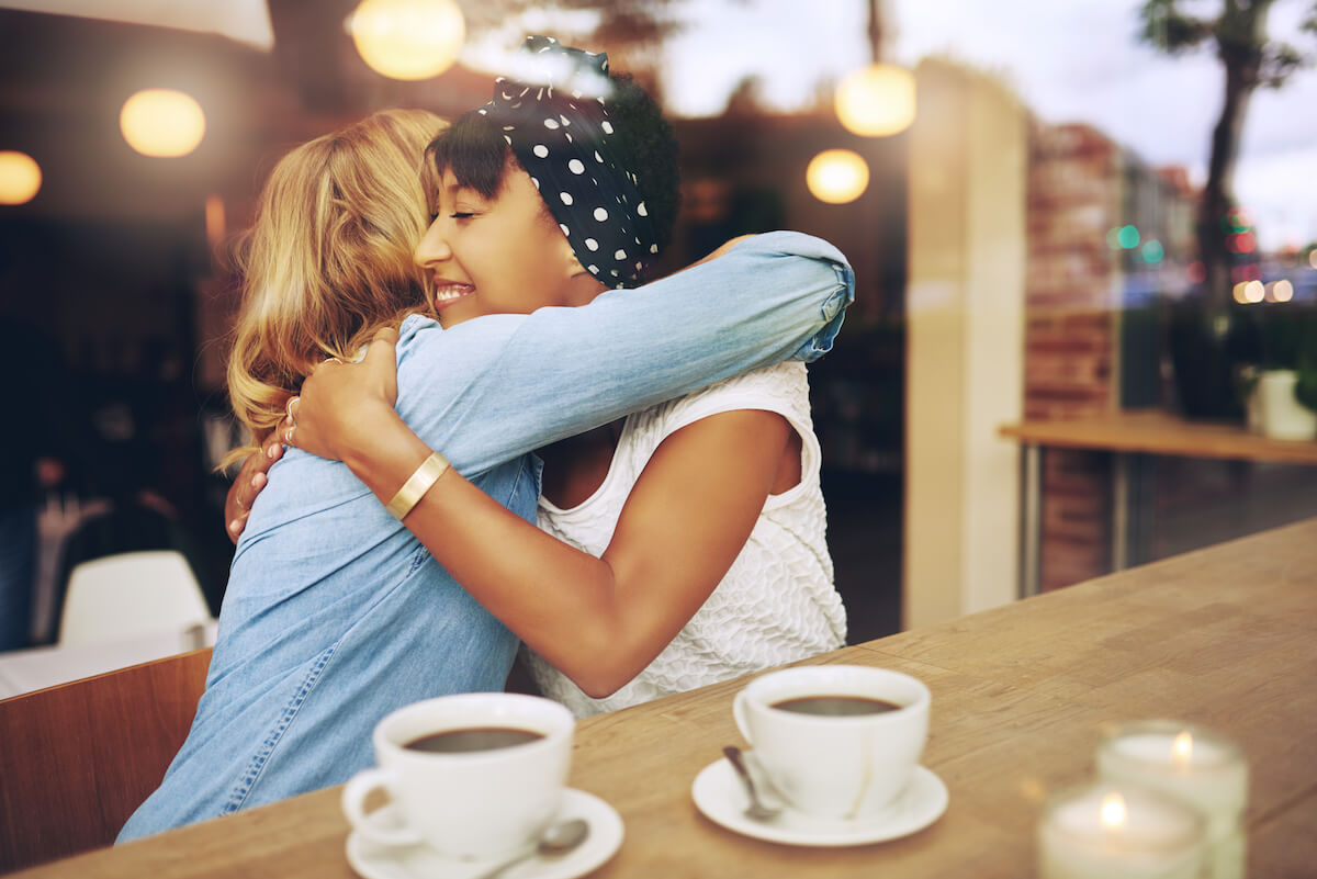 Shutterstock: Friends hugging and smiling meeting for coffee two women