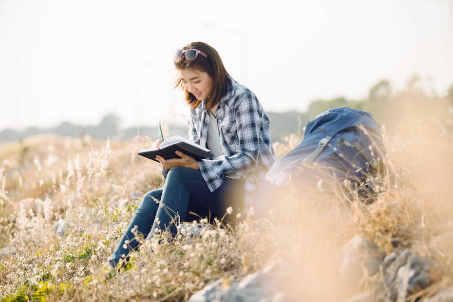 shutterstock-woman-backpacking-journaling-backpack-outdoors-032020