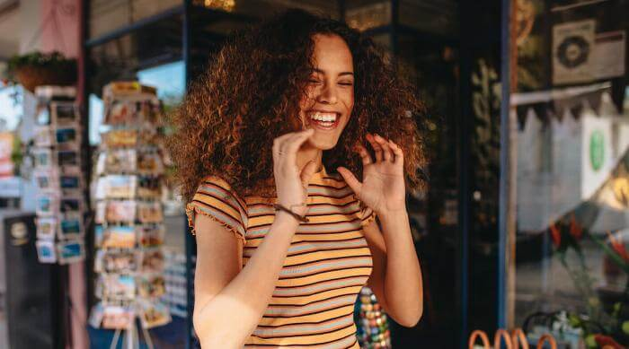 Shutterstock: Woman excited and smiling and laughing shopping outside on vacation