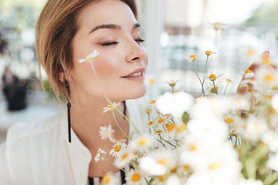 shutterstock-woman-inside-smelling-white-flowers-smiling-033120