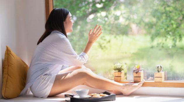 Shutterstock: Woman looking at nature staring out window with tea and cookies