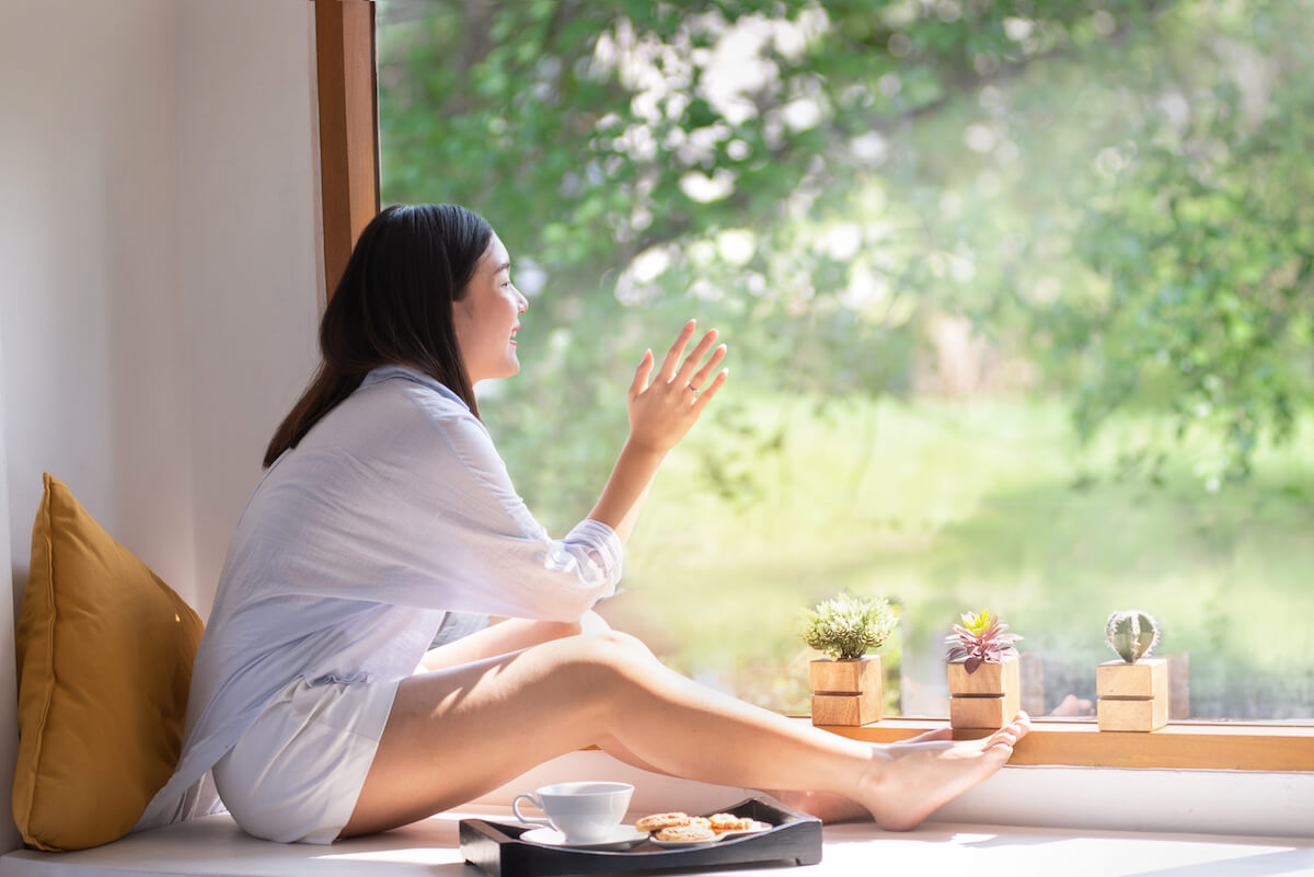 shutterstock-woman-looking-at-nature-out-window-tea-cookies