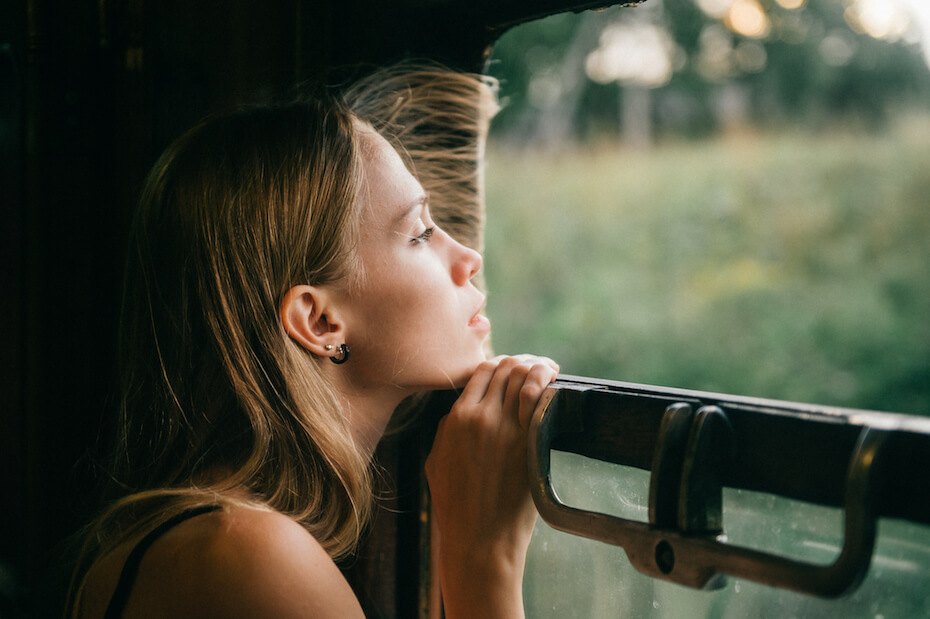 shutterstock-woman-looking-dreamily-out-window-at-green-033120