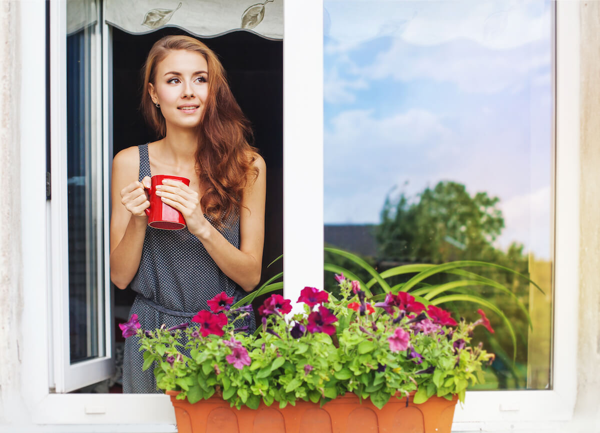 shutterstock-woman-looking-out-window-flowers-springjpg