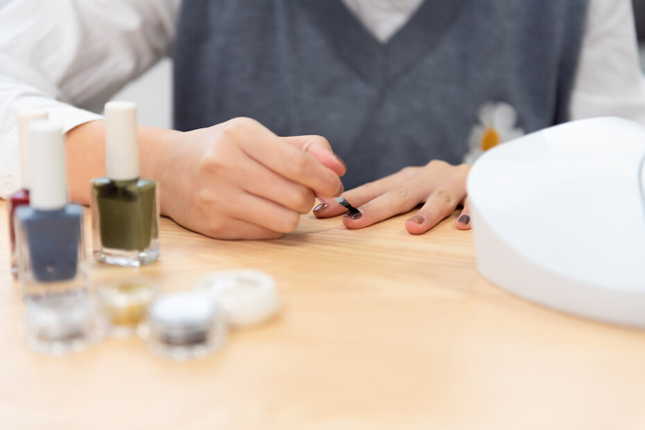 shutterstock-woman-painting-her-own-nails-on-table-032720