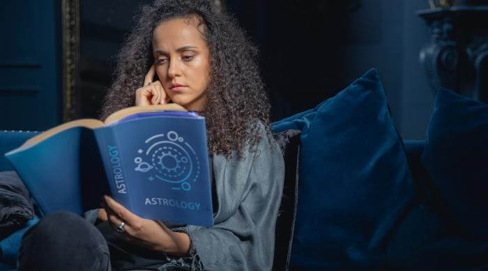 Shutterstock: Woman reading astrology book