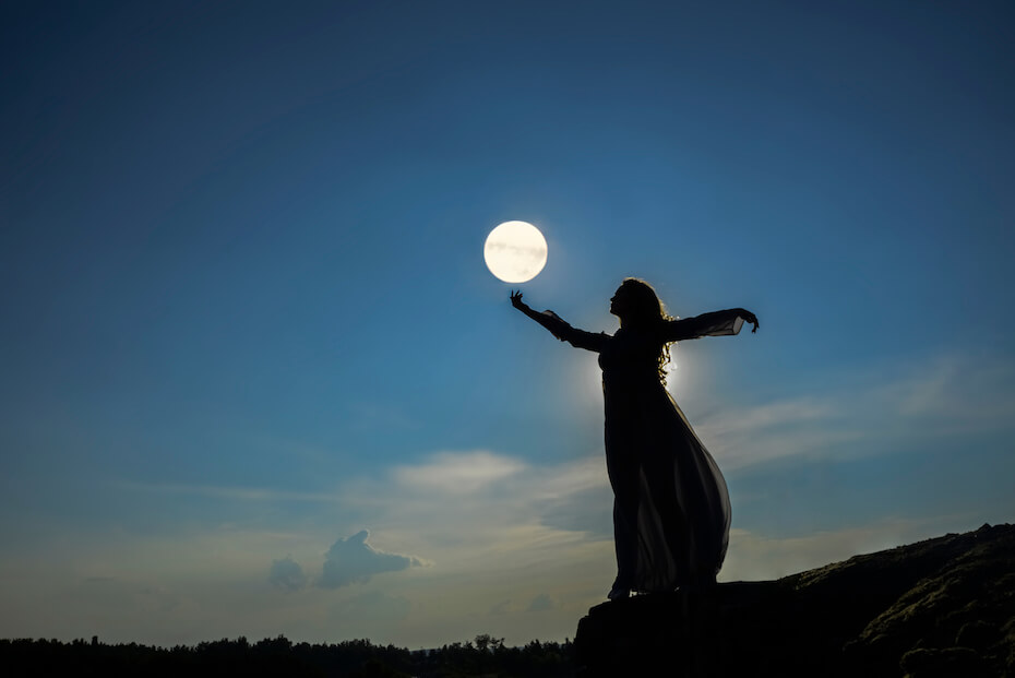 shutterstock-woman-silhouette-hands-up-to-full-moon-032020