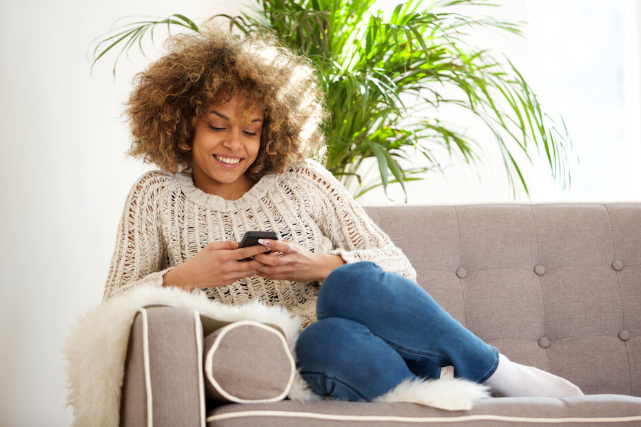 shutterstock-woman-smiling-looking-at-phone-on-couch-032420