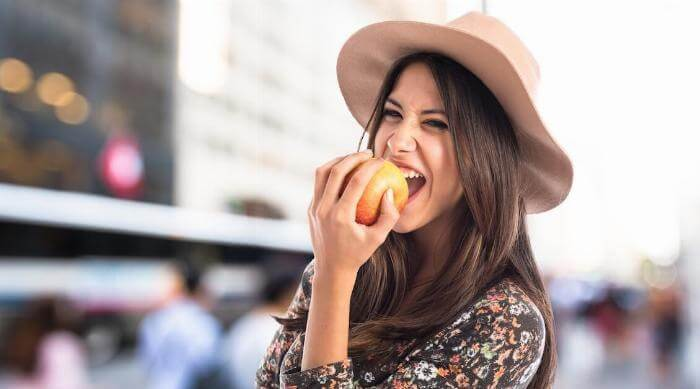 Shutterstock: Woman wearing hat eating an apple social