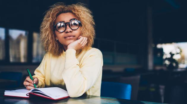 Shutterstock: Woman with glasses looking away daydreaming while writing in journal
