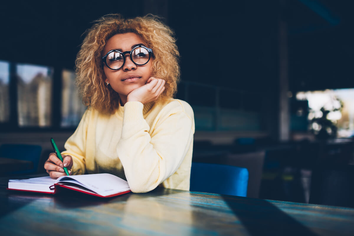 shutterstock-woman-with-glasses-looking-away-with-journal-writing-daydreaming