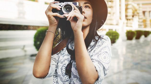 Shutterstock: Woman with nice camera taking pictures wearing a hat
