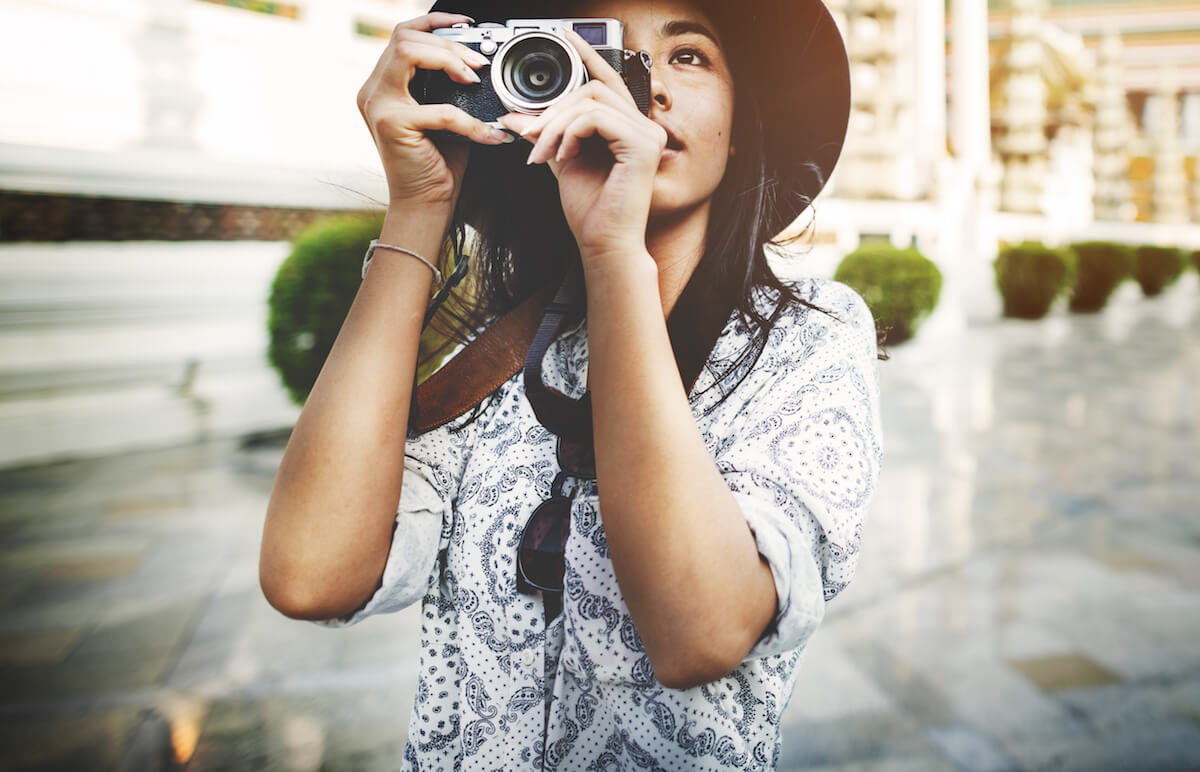 shutterstock-woman-with-nice-camera-taking-pictures-in-hat