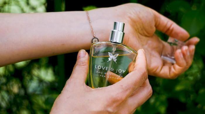Unsplash: Woman holding perfume fragrance bottle to her wrist