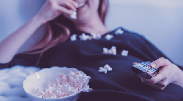 Woman lying on bed, holding remote, eating popcorn