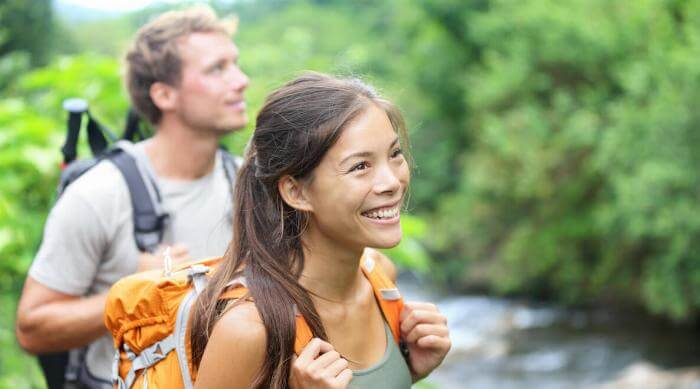 Shutterstock: Couple man and woman hiking smiling woman backpacking
