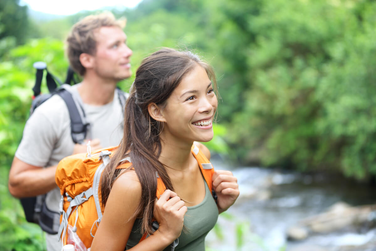shutterstock-couple-hiking-smiling-woman-backpacking