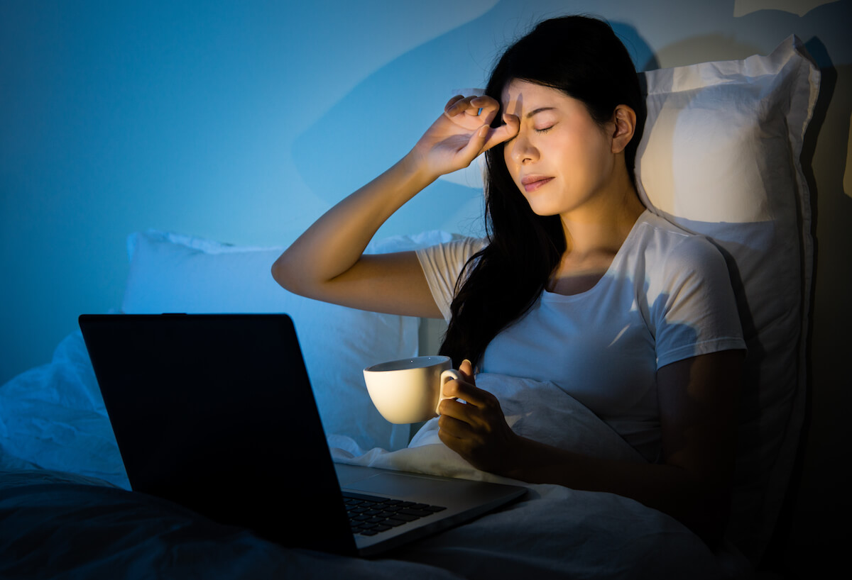 Shutterstock: Woman struggling to sleep at night with laptop and cup of coffee tea