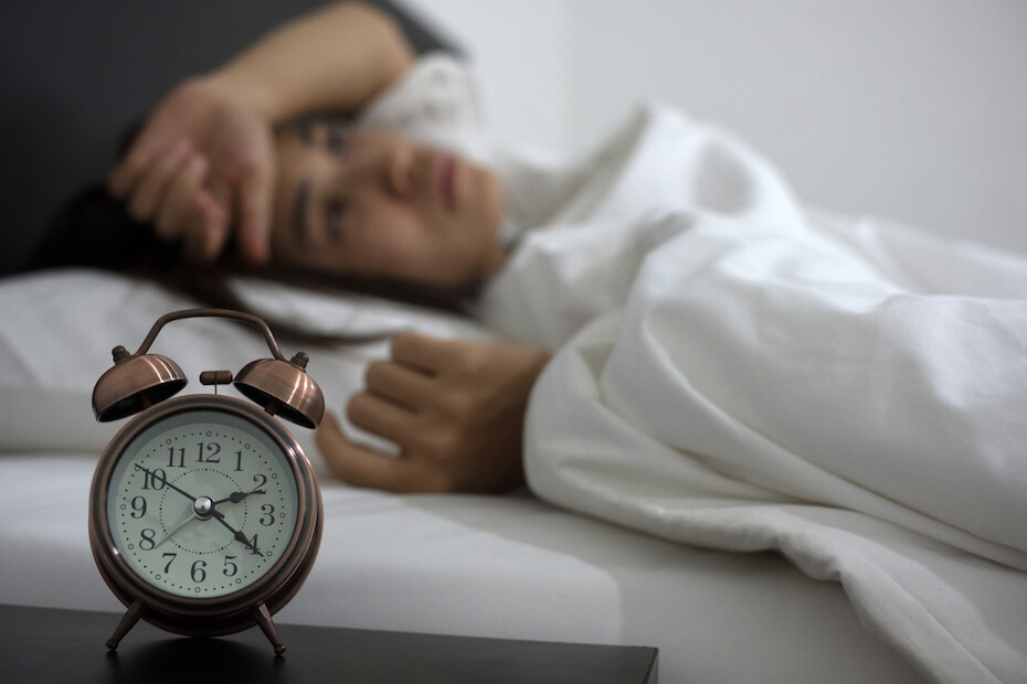 Shutterstock: Woman with alarm clock in bed can't sleep because of stress
