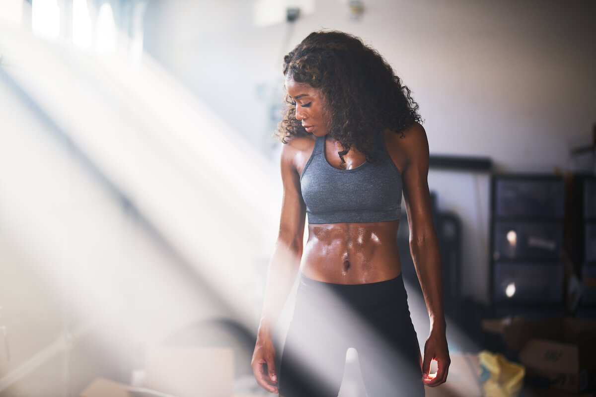 Shutterstock: Woman at home working out sweating