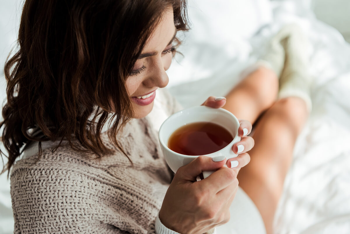 shutterstock-woman-clutching-coffee-tea-cup-in-bed