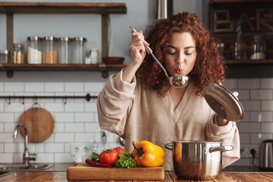 Shutterstock: Woman cooking dinner blowing on spoon tasting