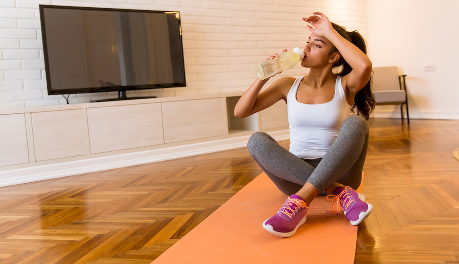 shutterstock-woman-in-workout-clothes-on-mat-drinking-water-042320