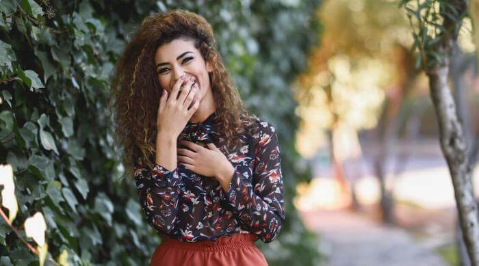 Shutterstock: Woman laughing covering mouth outside social