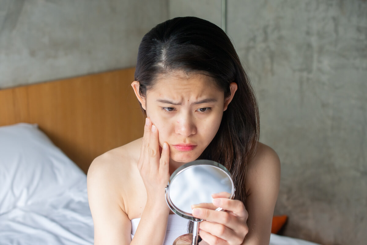 shutterstock-woman-pouting-over-pimple-in-mirror-stressed