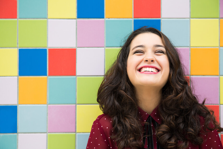 Shutterstock: Woman smiling happy in front of colorful tile wall