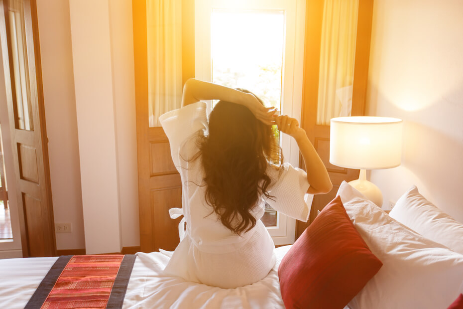 Shutterstock: Woman waking up restfully and happy in bed