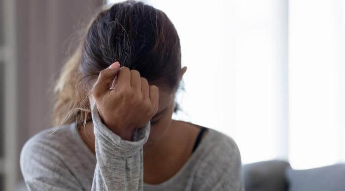 Shutterstock: Young woman looking stressed at home