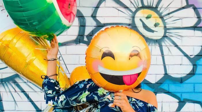 Woman holding emoji balloons