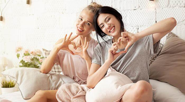 Shutterstock: Best friends hand hearts comfy at home