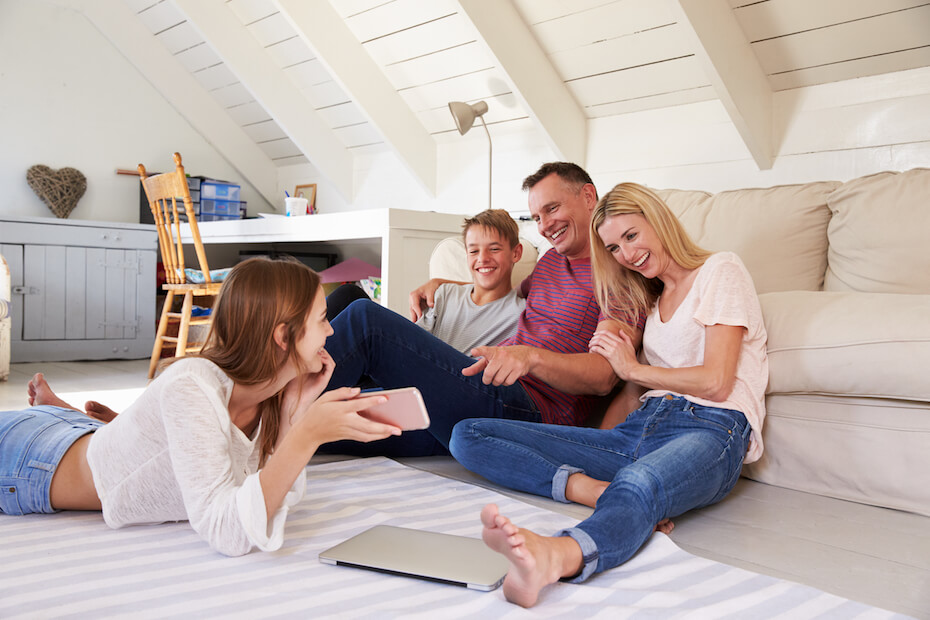 shutterstock-family-gathering-at-home-looking-at-phone-052220