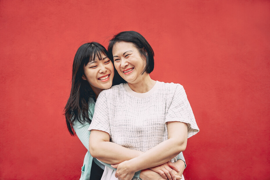 Shutterstock: Mom and daughter hugging and smiling in front of red wall