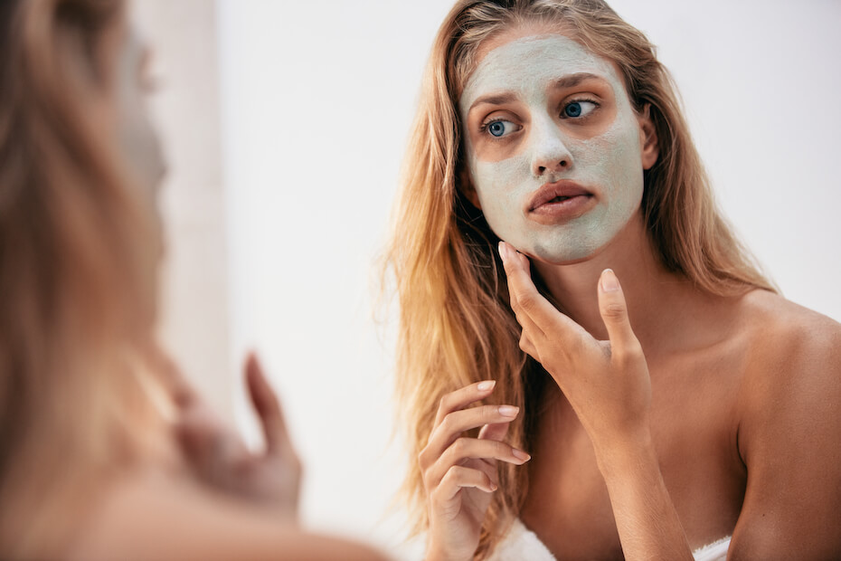 Shutterstock: Woman applying face mask in the bathroom