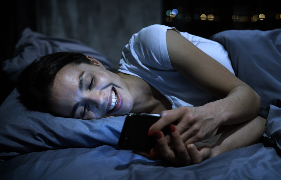 shutterstock-woman-before-bed-on-phone-texting-smiling-052220