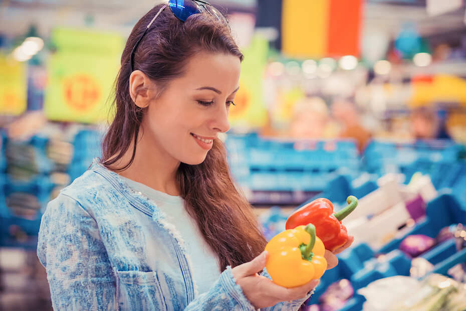 shutterstock-woman-holding-bell-peppers-grocery-store-051920