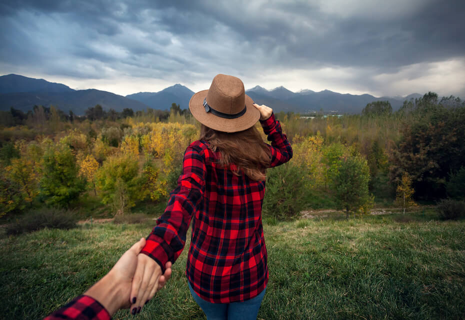 shutterstock-woman-holding-hand-behind-her-walking-to-cloudy-trees-mountains-051220