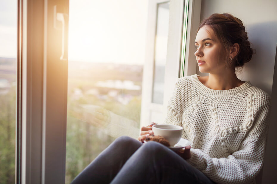 Shutterstock: Woman looking hopeful out a window drinking tea