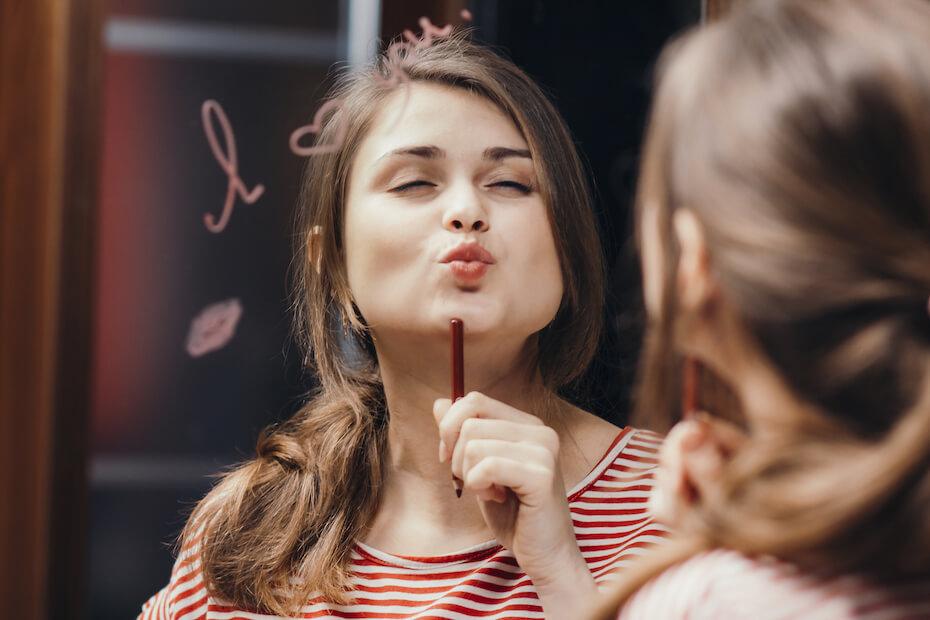 Shutterstock: Woman making kissy face in mirror
