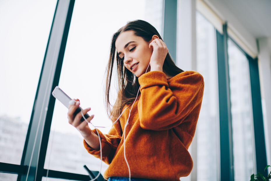 Shutterstock: Woman on phone listening to music on headphones