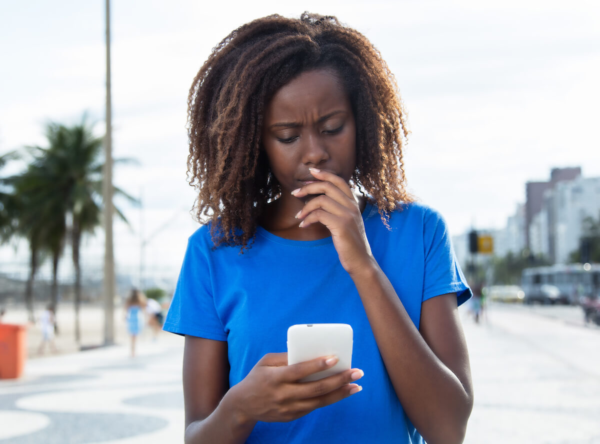 Shutterstock: Woman outside on phone looking upset and confused